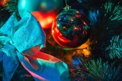 与五颜六色的照明设备的圣诞树和蝴蝶结分支与俏丽的球的 免版税库存照片