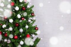 与五颜六色的球的圣诞树在白色砖墙和sno 免版税图库摄影