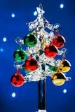 与五颜六色的球的玻璃圣诞树在被弄脏的光背景 免版税库存照片