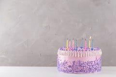 与五颜六色的盛开的蜡烛的桃红色生日蛋糕 库存图片