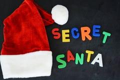 与五颜六色的磁性信件的秘密圣诞老人文本在Santa's红色帽子附近的黑板 库存图片
