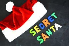 与五颜六色的磁性信件的秘密圣诞老人文本在Santa's红色帽子附近的黑板 库存照片