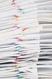 与五颜六色的纸夹交叠报告的关闭堆文书工作 免版税库存照片