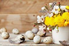与五颜六色的花、羽毛和鹌鹑蛋的愉快的复活节卡片在葡萄酒木背景 美好的春天构成 库存照片