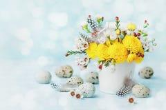 与五颜六色的花、羽毛和鹌鹑蛋的愉快的复活节卡片在葡萄酒绿松石背景 美好的春天构成 免版税库存照片