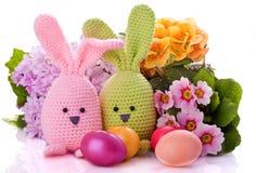 与五颜六色的花和复活节彩蛋的复活节兔子 免版税库存照片