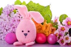 与五颜六色的花和复活节彩蛋的复活节兔子 库存照片