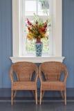 与花瓶和窗口的二把藤条椅子 库存照片