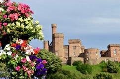 与五颜六色的花的因弗内斯城堡 因弗内斯,苏格兰 库存图片