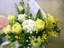 与五颜六色的花的构成 花yelloe郁金香,白色毛茛属,黄色含羞草 花在背景关闭隔绝 库存图片
