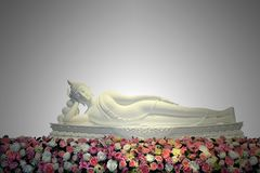 与五颜六色的花的白色斜倚的菩萨雕象在主要大厅里 免版税库存照片
