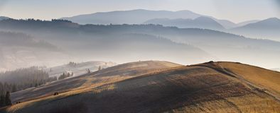 与五颜六色的草甸的山秋天日出全景风景 库存图片