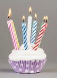 与五颜六色的蜡烛的杯形蛋糕 免版税库存照片