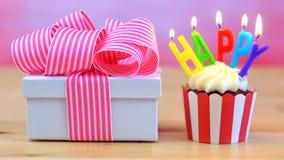 与五颜六色的蜡烛的生日快乐杯形蛋糕 库存图片
