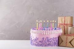与五颜六色的蜡烛的生日蛋糕在灰色背景 免版税图库摄影