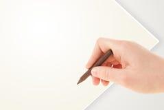 与五颜六色的蜡笔的儿童图画在空的白纸 库存照片