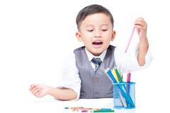 与五颜六色的蜡笔的逗人喜爱的男孩图画 库存照片