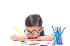 与五颜六色的蜡笔的逗人喜爱的男孩图画 免版税库存图片
