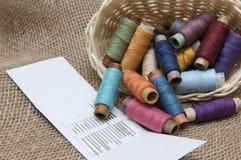 与五颜六色的螺纹的卷在一个柳条筐 免版税库存照片