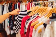与五颜六色的衣裳的晒衣架在妇女购物 另外的背景是蓝色蝴蝶装生动被更改的标志格式销售额天空夏天的星期日于罐中 免版税库存图片
