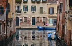 与五颜六色的角落、老走与伞的大厦、小船和人,意大利的威尼斯雨天 库存图片