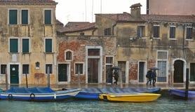 与五颜六色的角落、老走与伞的大厦、小船和人,意大利的威尼斯雨天 免版税库存照片
