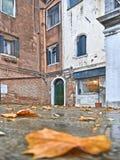 与五颜六色的角落、老走与伞的大厦、小船和人,意大利的威尼斯雨天 免版税图库摄影