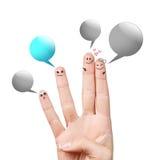 与五颜六色的讲话泡影的手指面带笑容 库存图片