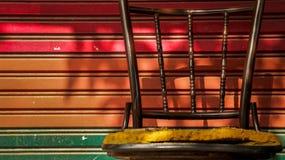 与五颜六色的路辗快门门的被放弃的葡萄酒金属椅子 免版税库存照片