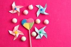 与五颜六色的轮转焰火和蛋白软糖的一个五颜六色的心脏形状棒棒糖在桃红色背景 免版税库存图片