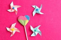 与五颜六色的轮转焰火的一个五颜六色的心脏形状棒棒糖在桃红色背景 免版税库存照片