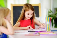 画与五颜六色的铅笔的两个逗人喜爱的妹在托儿 一起绘创造性的孩子 库存照片