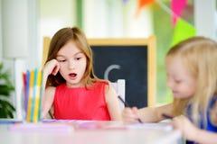 画与五颜六色的铅笔的两个逗人喜爱的妹在托儿 一起绘创造性的孩子 免版税图库摄影