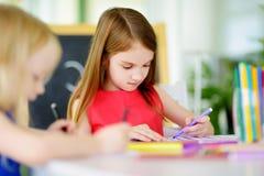 画与五颜六色的铅笔的两个逗人喜爱的妹在托儿 一起绘创造性的孩子 库存图片