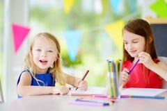 画与五颜六色的铅笔的两个逗人喜爱的妹在托儿 一起绘创造性的孩子 图库摄影