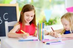 画与五颜六色的铅笔的两个逗人喜爱的妹在托儿 一起绘创造性的孩子 免版税库存图片
