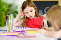 画与五颜六色的铅笔的两个逗人喜爱的妹在托儿 一起绘创造性的孩子 免版税库存照片