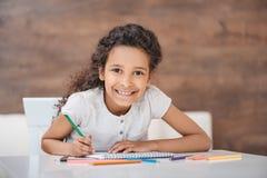 与五颜六色的铅笔的可爱的非裔美国人的女孩图画 免版税库存图片