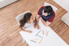 与五颜六色的铅笔的父亲和女儿图画,当在家时坐在桌上 图库摄影
