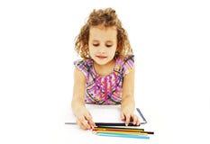 与五颜六色的铅笔的被吸收的小女孩图画 库存照片