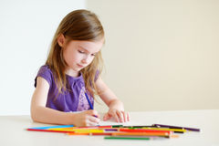 画与五颜六色的铅笔的逗人喜爱的女孩一张图片 免版税图库摄影