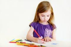 画与五颜六色的铅笔的逗人喜爱的女孩一张图片 免版税库存图片