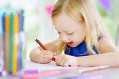 与五颜六色的铅笔的逗人喜爱的小女孩图画在托儿 创造性的孩子绘画在学校 免版税库存图片