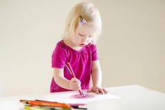 与五颜六色的铅笔的逗人喜爱的小孩女孩图画 免版税库存照片