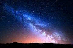 与五颜六色的银河的夜风景和在山的黄灯 与小山的满天星斗的天空在夏天 美丽的宇宙 空间