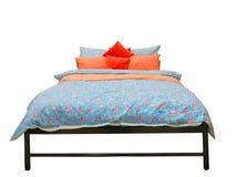 与五颜六色的鸭绒垫子和坐垫的床 免版税库存图片