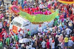 与五颜六色的龙的汉语灯节,狮子,旗子,汽车,在街道被吸引的人群前进了 免版税图库摄影