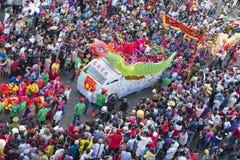 与五颜六色的龙的汉语灯节,狮子,旗子,汽车,在街道被吸引的人群前进了 图库摄影