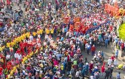 与五颜六色的龙的汉语灯节,狮子,旗子,汽车,在街道被吸引的人群前进了 库存照片