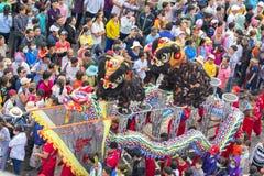 与五颜六色的龙的汉语灯节,狮子,旗子,汽车,在街道被吸引的人群前进了 免版税库存照片